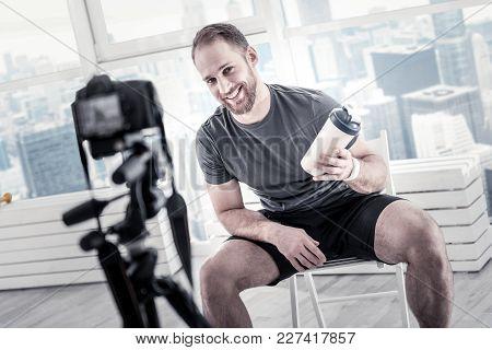 After Training Program. Optimistic Vigorous Male Blogger Showing Bottle While Holding It And Smiling
