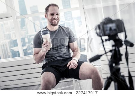 Proteins In Bottle. Jolly Optimistic Male Blogger Having Bottle While Smiling And Resting