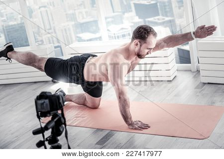 Unusual Stretching. Handsome Confident Male Blogger Rising Hand And Leg While Training And Having Bl