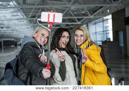 Waist Up Portrait Of Female Companions Using Smartphone On Selfie Stick. They Are Smiling And Gestur