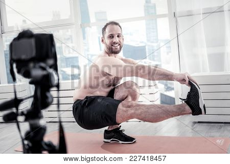 Also Do It. Enthusiastic Vigorous Male Blogger Holding Leg While Smiling And Gazing At His Camera