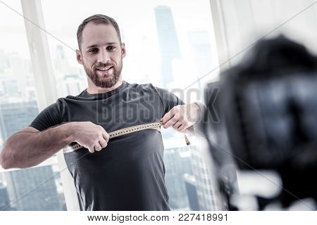 Another Centimeter. Charming Bearded Male Blogger Using Meter While Standing In Front Of Camera And