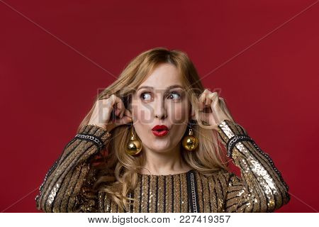 Portrait Of Wondered Female Person Putting On Christmas Tree Decorations Instead Of Eardrops. Isolat