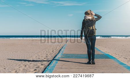 Sunny Day. Back View. Young Woman Tourist In A Hat And With A Backpack Standing On The Seashore And