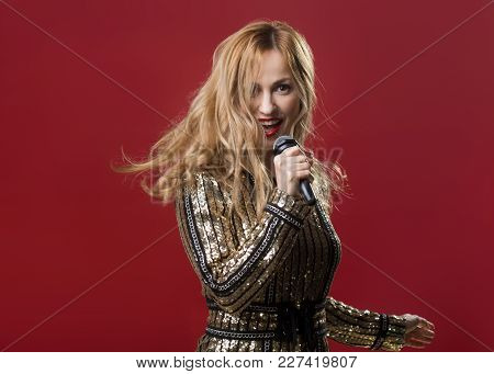 Waist Up Of Happy Lady Dancing And Singing Into The Microphone. Copy Space In Left Side. Isolated On