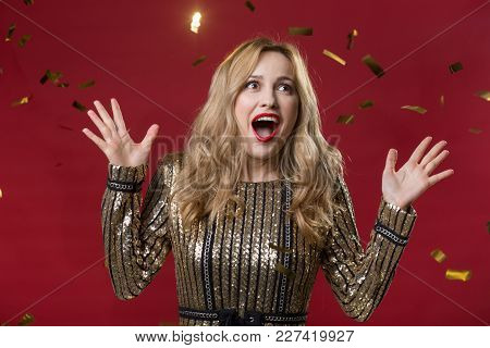 Waist Up Portrait Of Amazed Girl Wearing Beautiful Dress. Her Eyes Wide Opened And Hands Raised With