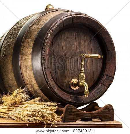 Beer barrel with bunch of wheat on the wooden table. Clipping path.