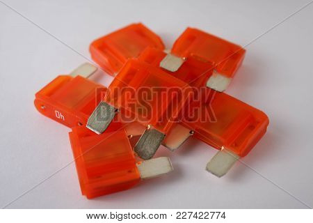 Multiple Orange Car Fuses On White Background, Close Range View