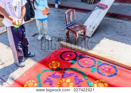 Antigua, Guatemala -  April 13, 2017: Spraying Water On Holy Thursday Dyed Sawdust Procession Carpet