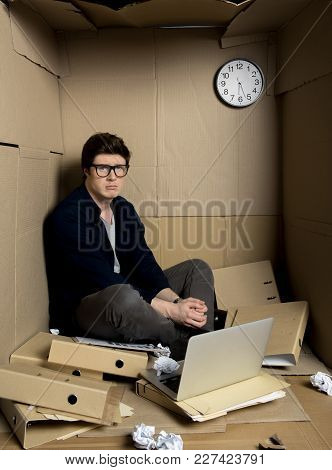 Chaos At Work Concept. Full Length Portrait Of Young Manager Is Sitting With Laptop Inside His Confi