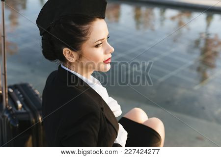 Attractive Young Girl Stewardess In Uniform Waiting For Her Flight, Looking Up Into The Sky