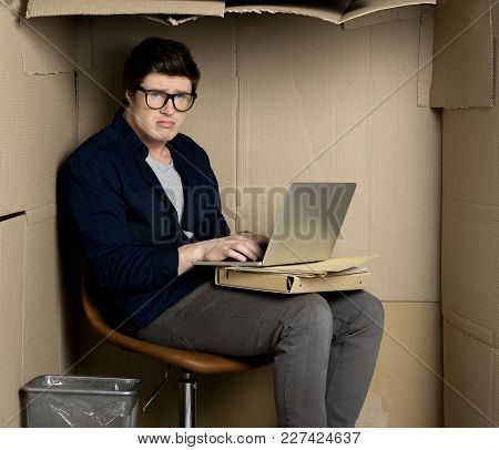 No Space Concept. Portrait Of Depressed Employee Is Sitting In Cramped Carton Office And Typing On L
