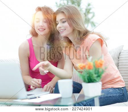 two young women talking and sitting down at the coffee table