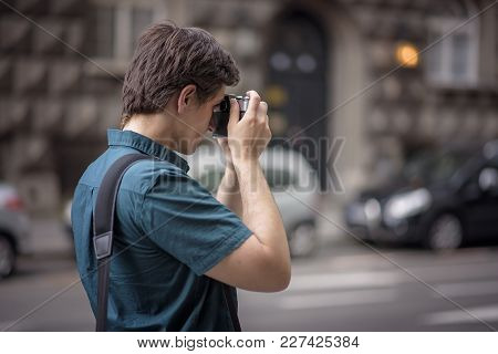 Young Attractive Man, A Photographer, Taking Photographs In An Urban Area With An Analog Slr Camera