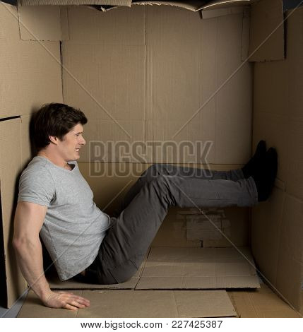 Need More Space Concept. Full Length Of Young Man Is Sitting In Cardboard Box While Pushing The Wall