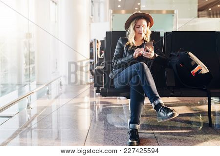 Young Woman Tourist In Hat, With Backpack Sits At Airport Near Window And Uses Smartphone. Hipster G