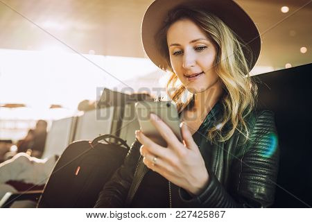 Young Woman Tourist In Hat, With Backpack Sits At Airport And Uses Smartphone. Hipster Girl Is Waiti