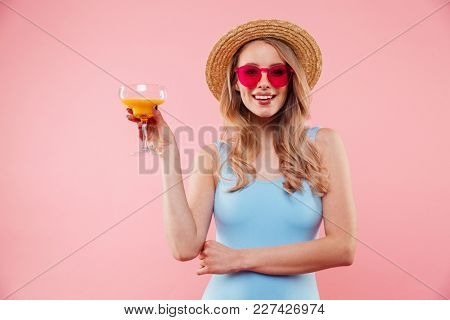 Gorgeous lady in sunglasses wearing one-piece blue swimsuit and straw hat smiling while holding glass of orange juice isolated over pink background