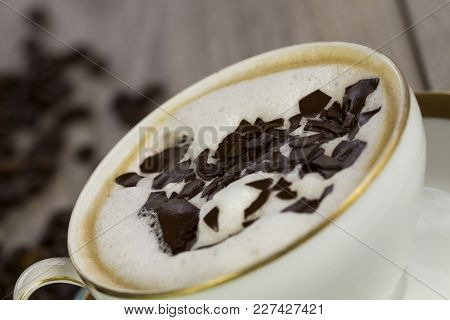 Cup Of Freshly Brewed Aromatic Cappuccino Coffee Topped With Milky Froth And Grated Chocolate Flakes