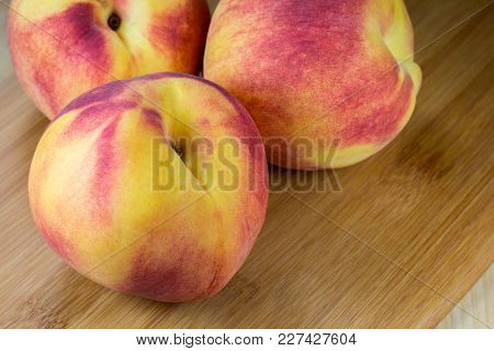 Fresh, Whole Nectarines Arranged Together As A Bunch On A Bamboo Cutting Board.