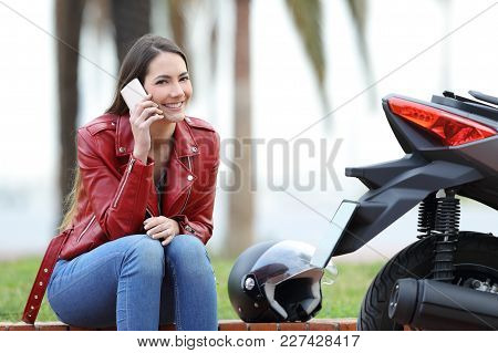 Happy Motorbiker Calling Insurance On Phone After Breakdown And Looking At Camera Sitting Beside Her