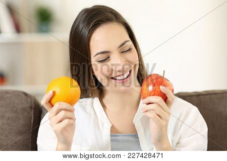 Front View Portrait Of A Happy Woman Deciding Between Orange And Apple Sitting On A Couch In The Liv