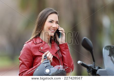 Happy Motorbiker Calling On Mobile Phone Sitting On A Motorbike