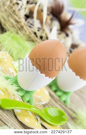 Two Hard Or Soft Boiled Brown Eggs In Egg Cups Next To Basket Of Eggs With Feathers On Wooden Surfac