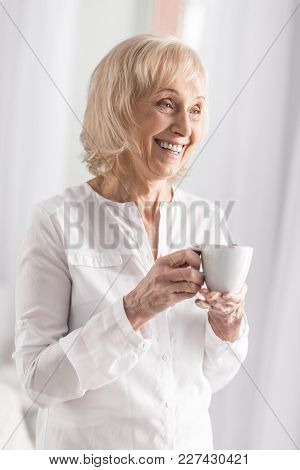 Coffee Odor. Gay Optimistic Mature Woman Smiling While Enjoying Coffee And Posing On Light Backgroun