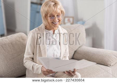Important Documentation. Joyful Glad Mature Businesswoman Wearing Glasses While Examining Papers And