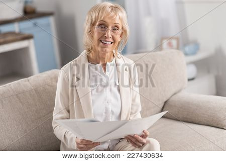 Business Documentation. Gorgeous Beautiful Mature Businesswoman Looking At Camera While Holding Pape