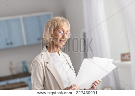 Hard Work. Pretty Glad Mature Businesswoman Putting On Glasses While Gazing Down And Holding Papers
