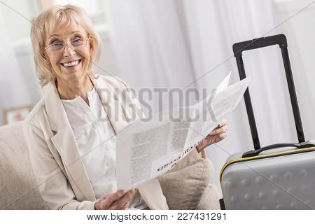 Good News. Energetic Experienced Mature Woman Posing Near Suitcase While Having Newspaper And Lookin