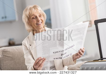 Excellent Article. Beautiful Merry Mature Woman Sitting Near Suitcase While Looking At Article And S
