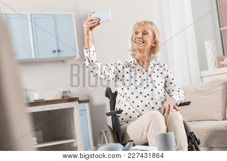Best Selfie. Cheerful Mature Disabled Woman Taking Photo In Wheelchair While Saving Memory And Shari