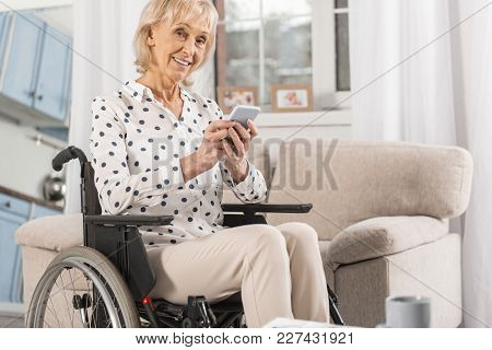 Stay Active. Cheerful Handicapped Mature Woman Typing Message In Wheelchair While Staring At Camera