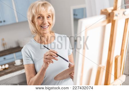 Drawings For Relaxation. Optimistic Energetic Mature Woman Smiling While Holding Tassel And Painting