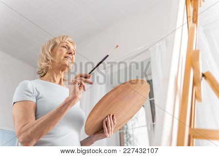 Creating Process. Low Angle Of Appealing Pleasant Mature Woman Carrying Palette And Tassel While Sta