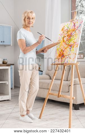 Age No Matter. Beautiful Creative Mature Woman Standing Near Easel While Using Tassel And Palette An