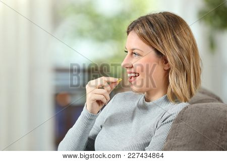 Profile Of A Happy Woman Taking A Vitamin Pill Sitting On A Couch In The Living Room At Home