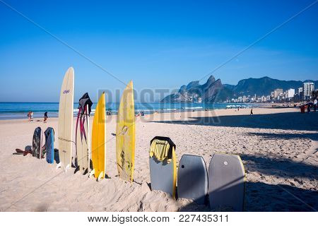 Surfboards Standing Upright In Bright Sun On The Ipanema Beach, Rio De Janeiro, Brazil