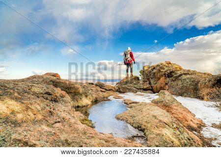 mature backpacker on a mountain ridge in winter scenery - Horsetooth Rock trail above Fort Collins in northern COlorado