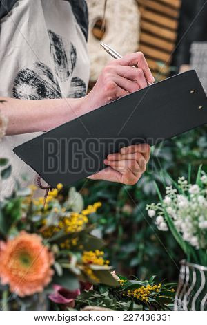 Crop Woman In Apron Writing On Clipboard While Working In Floral Shop.