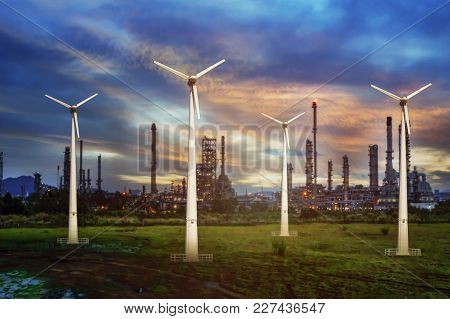Wind Turbine With Oil Refinery At Twilight Sky Background.