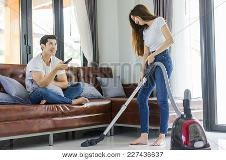 Asian Couple Girl Doing Floor Cleaning With Vaccuum Cleaner While Man On A Brown Sofa At Home Using