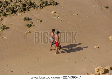 ALBUFEIRA, PORTUGAL - AUGUST 23, 2017: Couple walking at the beach of Olhos de Agua in Albufeira. This beach is a part of famous tourist region of Algarve.
