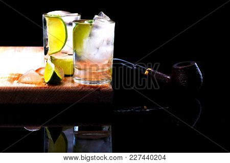 Yhe Two Shots Of Strong Alcohol On A Wooden Board, Inside Which The Ice Cubes And Lime, Cut Into Wed