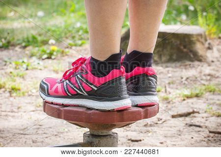 Legs Of Elderly Senior Woman In Sports Shoes Exercising On Outdoor Gym, Trainer Machine, Healthy, Sp