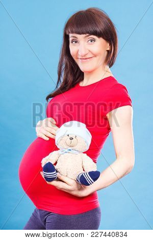 Happy Smiling Pregnant Woman Holding Toy Teddy Bear, Concept Of Expecting For Newborn And Extending