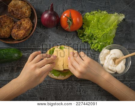 The Girl Puts The Cheese In The Manufacture Of Hamburger. Cooking Hamburger For School Lunch Child.